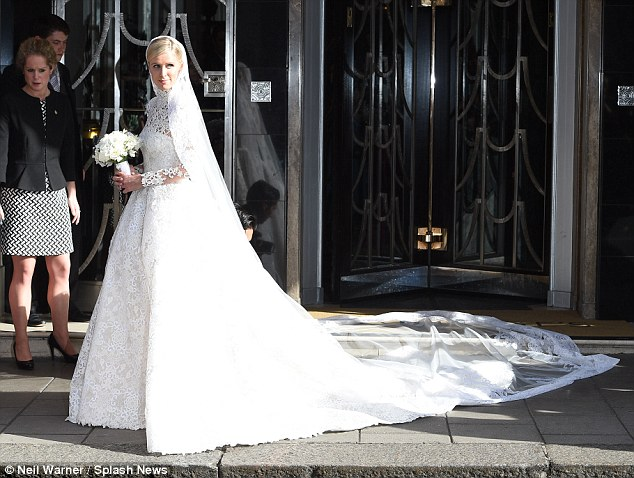Here comes the bride: Nicky was also photographer leaving her hotel in a white gown and veil
