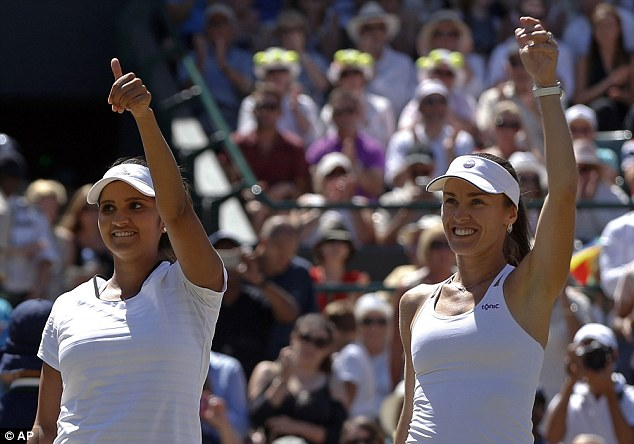 Martina Hingis (right) andSania Mirza (left) raise their hands after reaching the Wimbledon doubles final