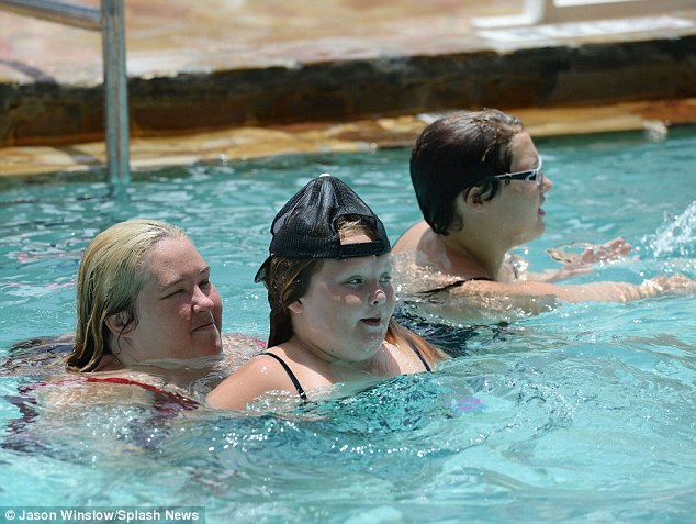 New accessory: Alana proudly wore the baseball cap in the pool