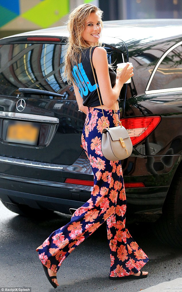 That's just rude: Behati Prinsloo stuck her tongue out as she went shopping for groceries in New York on Thursday wearing eye-catching blue floral trousers that harked back to the Sixties