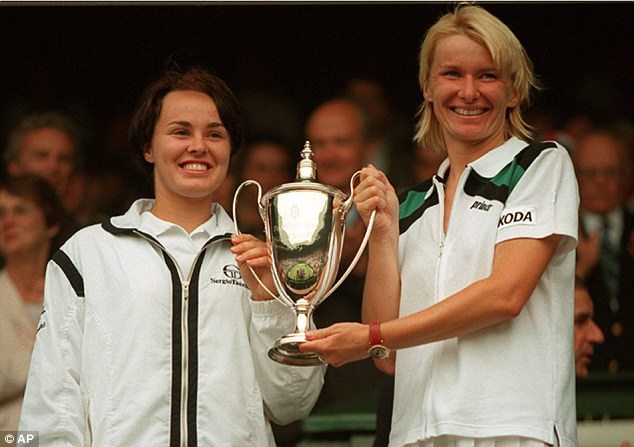 Hingis holds the trophy with partner Jana Novotna after winning the doubles title 17 years ago