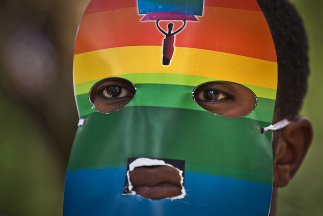 FILE - In this Monday, Feb. 10, 2014 file photo, a Kenyan gay man wears a mask to preserve his anonymity as he and others stage a rare protest, against Ugand...