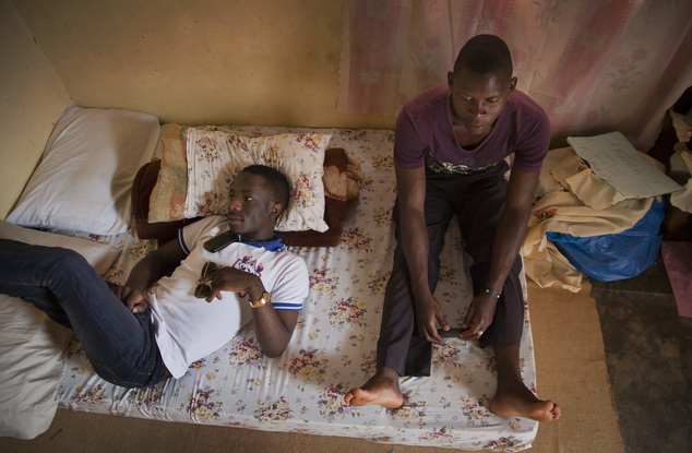FILE - In this Tuesday, March 25, 2014 file photo, two Ugandan homosexual men sit in the one-room safe-house where they live, at an undisclosed location in U...