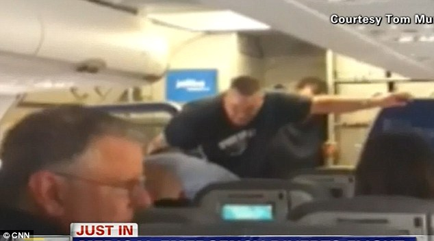 The captain is restrained by passengers in the aisle as the plane makes an emergency landing
