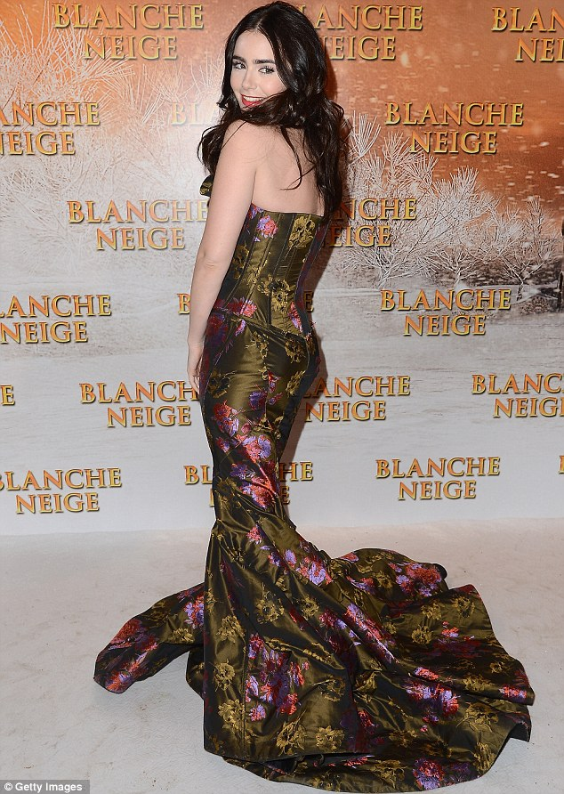 Opulent: Lily's satin gown was festooned with flowers and a very apt forest green