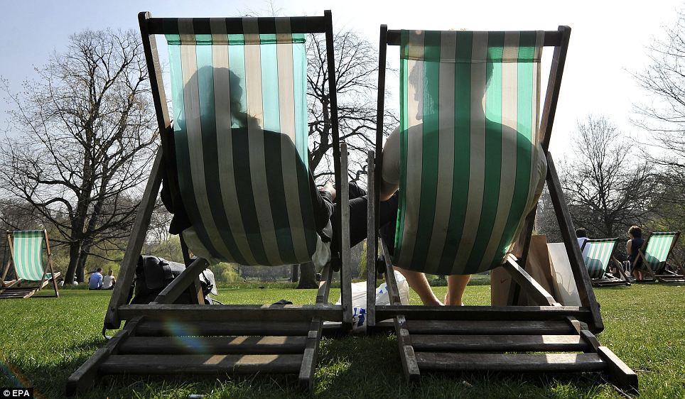 Soaking up the sun: A couple enjoy the rays as they sit in deck chairs in St James's Park... but not for much longer