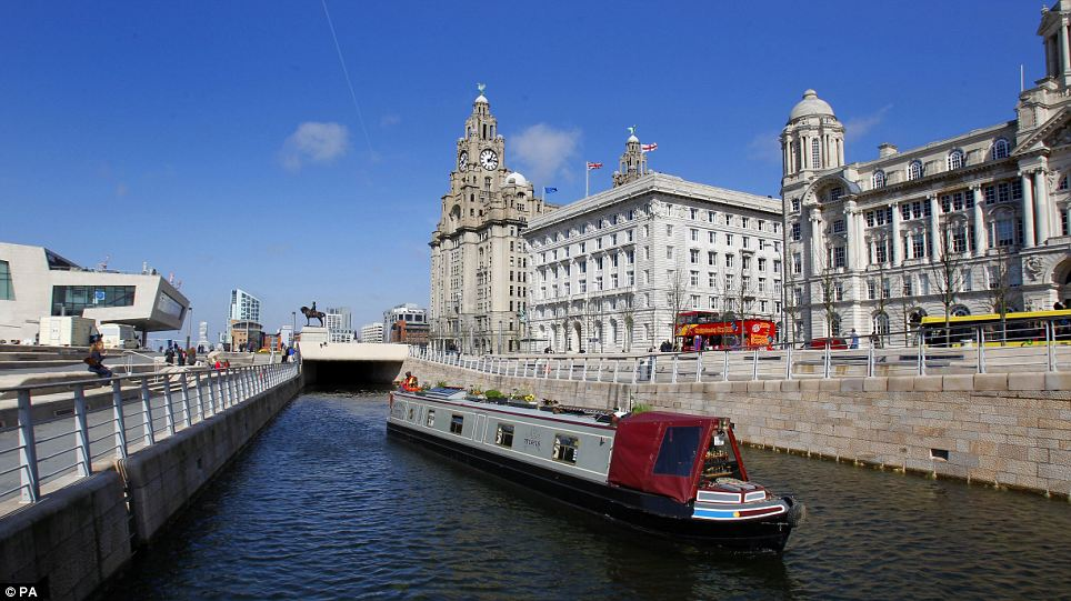 A Canal Boat cruises on the water at The Albert Dock, Liverpool as the sunny but crisp weather continues across the UK