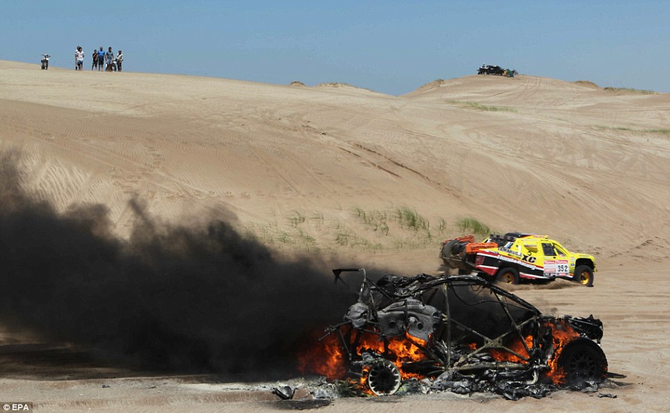 The car of South African driver Alfie Cox sits burning during the first stage of the Rally Dakar 2012 between Mar del Plata and Santa Rosa