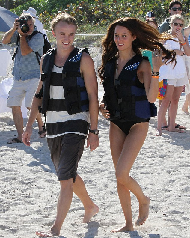 Showing her off! Tom Felton wore a wide grin as he walked across a Miami beach with his girlfriend Jade Olivia on New Year's Day
