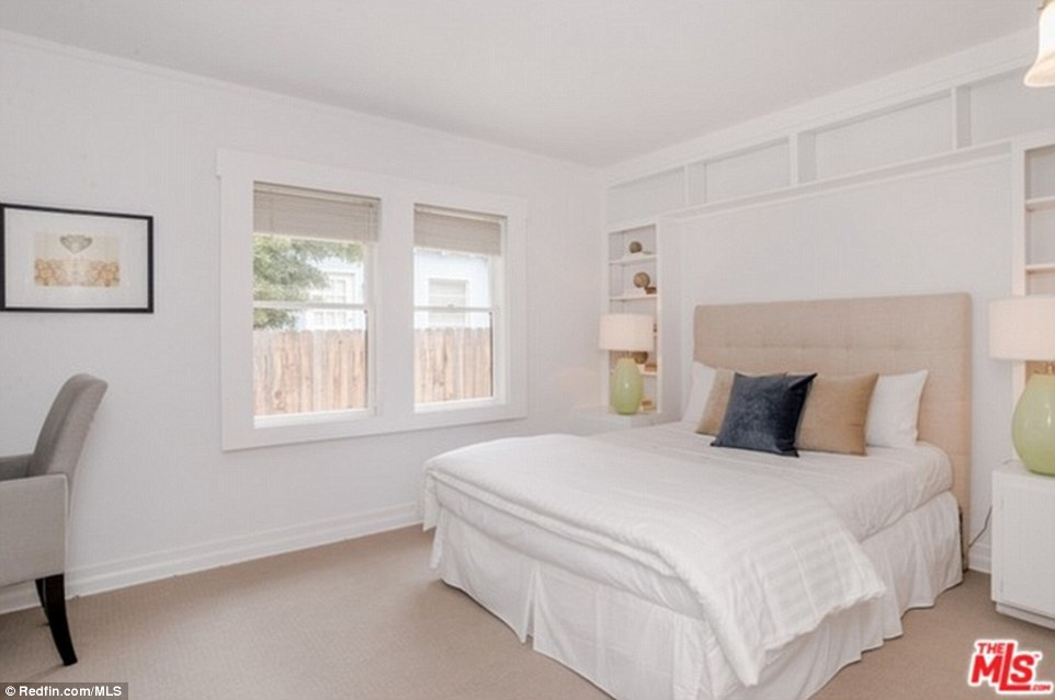 Another bedroom boasts two windows, decorative storage space around the bed and white walls