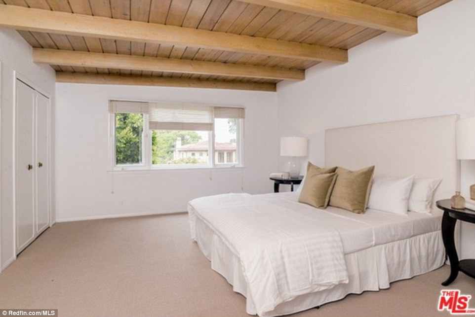 A fourth bedroom has wood beams, a closet with double doors and a window looking out onto what appears to be the front side of the house