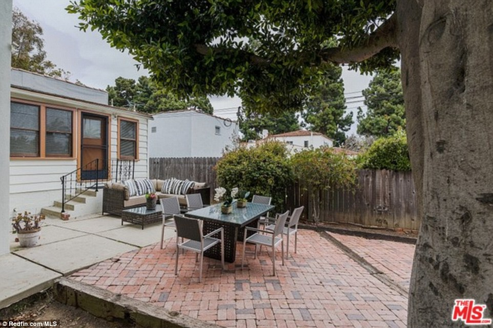 The fenced backyard includes a brick and concrete patio with dining and seating areas as well as tall trees
