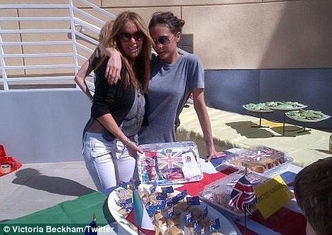 Flying the flag: Posh and her friend Suzie serving lunch at her children's school's International Food Day
