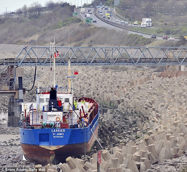 The ship, seen at low tide today, is now resting against the sea defences on the side of the bay