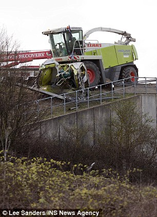 Perilous: The A34 in Oxford was closed for a significant period yesterday as emergency services worked to remove the combine harvester from its dangerous position
