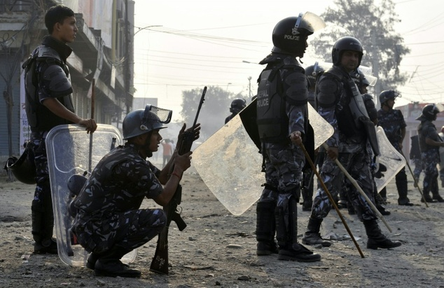 Nepalese riot police watch protesters near the Nepal-India border, some 90 km south of Kathmandu, on November 4, 2015