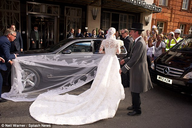 Manic moment: The bride's beautiful lace veil and the train of the £50,000 dress gets caught underneath the wheel of the bridal car
