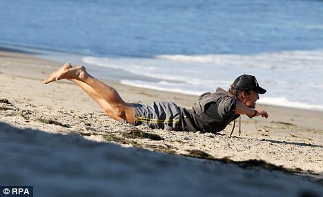 Bendy: Matthew McConaughey enjoys a spot of yoga on the beach - but could he be doing his body more harm than good?