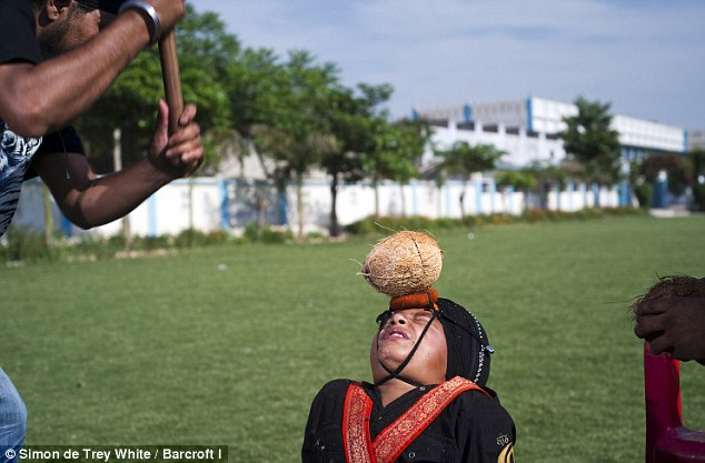He must be nuts! Ten-year-old Manpreet Singh winces in anticipation as his uncle prepares to smash a coconut on the youngster's forehead with a baseball bat