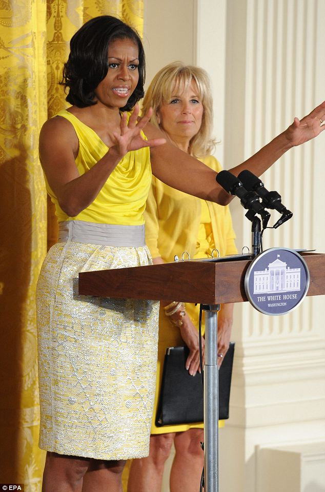 Colour co-ordination: While the first lady bared her arms in a yellow cowl-neck dress which had a contrasting textured gold skirt, Mrs Biden wore a simple yellow cardigan over a bow-detailed shift dress, in front of a matching White House curtain