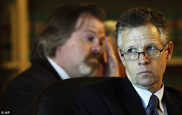 Legal team: Mark Quigley, right, and Travis Currie, left, attorneys for Steve Powell, view photos projected on a courtroom screen during Powell's voyeurism trial
