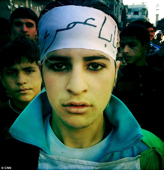 Rebels: A teenager, his eyes thick with kohl, gathers for a Friday demonstration in the Baba Amr district