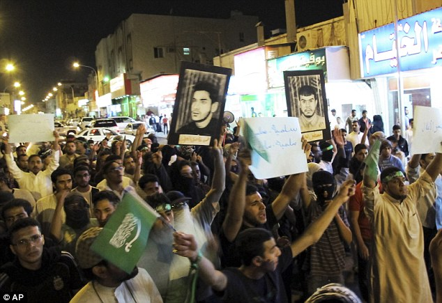 Unrest: Saudi Shiite protesters hold Saudi flags and portraits of Saudi Shiite prisoners during a demonstration in Qatif last March. British MPs are concerned about arms deals with the country given the disturbances there
