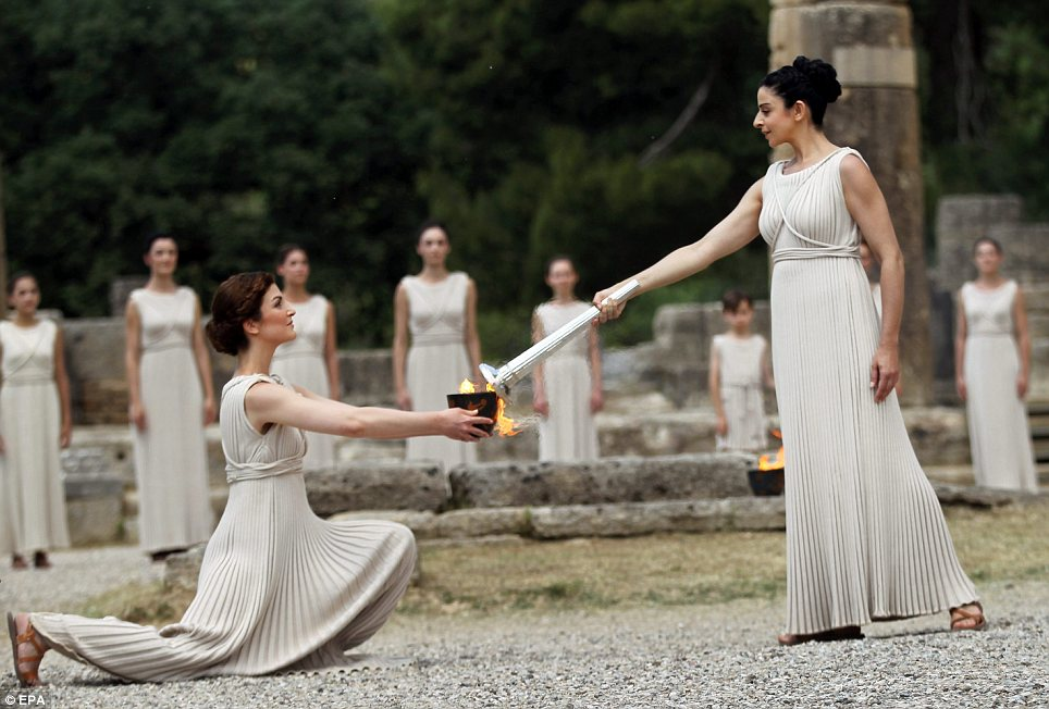 And so it begins: Actress Ino Menegaki (right), in the role of the High Priestess, lights the torch of the Olympic Flame during the Lighting Ceremony in front of the Hera Temple in Ancient Olympia
