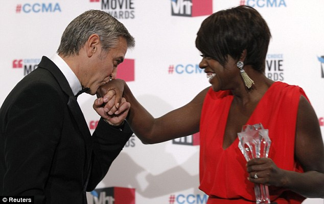 A winner's kiss: George Clooney gallantly congratulates Viola backstage