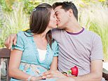 A stock photo of a couple kissing on park bench.     Image shot 2010. Exact date unknown.