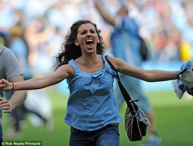 Jubilation: This ecstatic woman joins a host of other celebratory Manchester City fans on the pitch after their team's unbelievable win