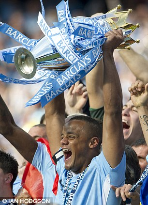 Champions: City captain Vincent Kompany lifts aloft the trophy after a nail biting finish