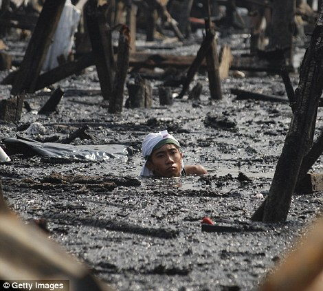 Dangerous: Residents waded into the ash-covered water in Manila's Tondo district to salvage any belongings floating among the debris