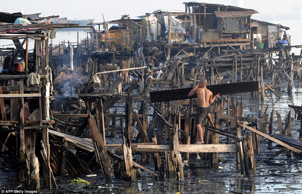 Wreckage: Residents of the sprawling shanty town search for belongings after a huge fire turned their wooden huts to charred timber