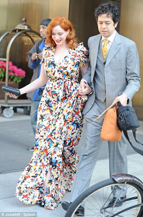 Dolled up: Christina sported a floor-length floral dress for the wedding while her husband looked dapper in a grey suit