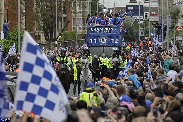 Flying high: Chelsea fans wave their plastic blue flags to welcome home their European heroes