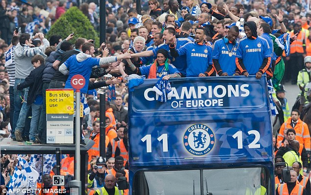 Meeting their heroes: Chelsea fans stand on top of a bus stop and manage to shake hands with skipper Terry
