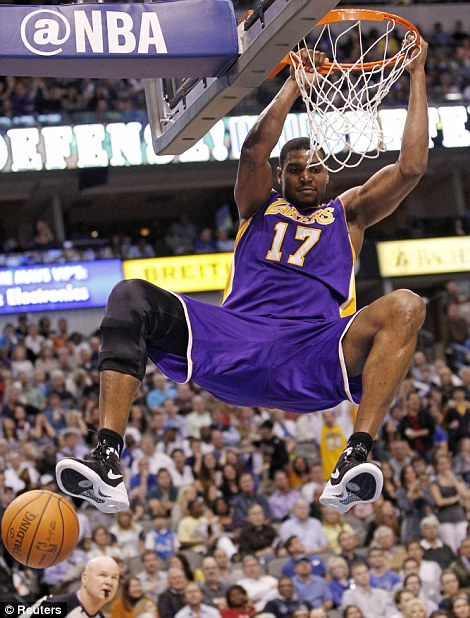 LA Lakers centre Andrew Bynum hangs on the rim after a slam against Dallas