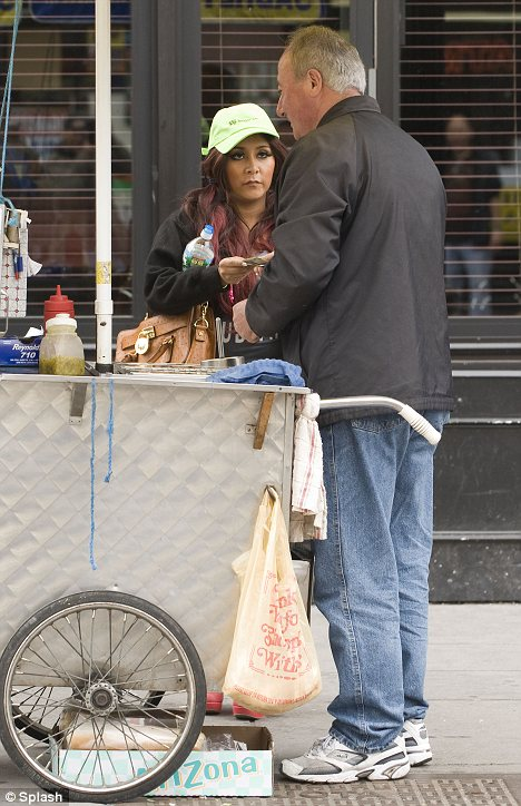 Irresistible: Snooki tucked into a tasty treat as she stopped after spotting the street vendor
