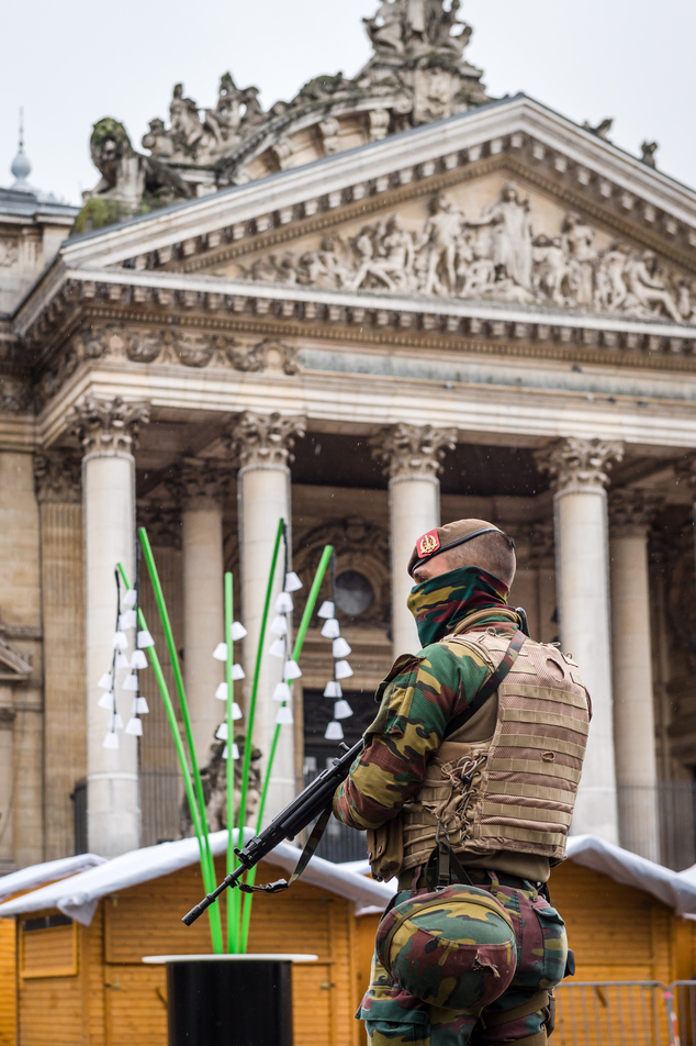 A Belgian Army soldier patrols near Christmas huts in front of the old Brussels' stock exchange on Sunday, Nov. 22, 2015. Western leaders stepped up the rhet...