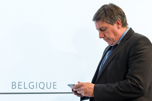 Belgium's Interior Minister Jan Jambon checks his phone as he leaves during media briefing after a National Security Council meeting in Brussels on Sunday, N...