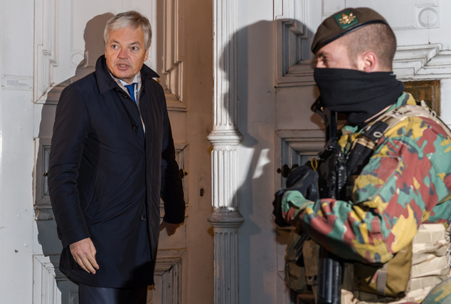Belgian Foreign Minister Didier Reynders, left, walks by a soldier from the Belgian Army as he arrives to take part in a National Security Council meeting in...