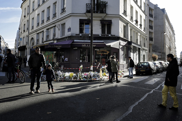 People pay respect to the victims in front of the 'Casa Nostra' restaurant in Paris, just over a week after the start of the Paris attacks, Sunday, Nov. 22, ...