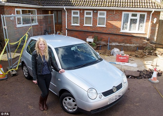 Good as new: Zoe Smith, 19, with her new car after her local council filled in a 30ft hole with concrete