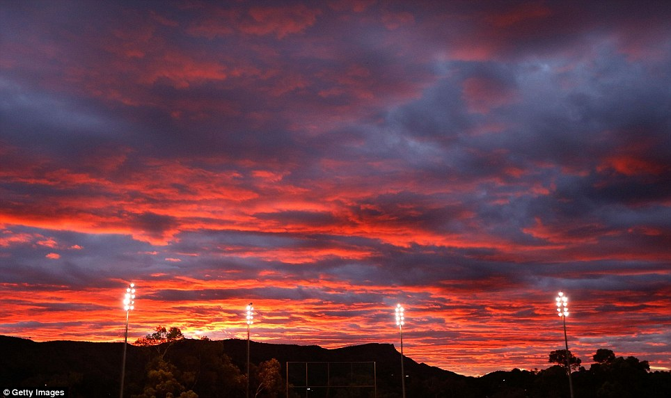 Red sky at night: The sun sets over Traeger Park during the cricket Imparja Cup Final between New South Wales and Western Australia