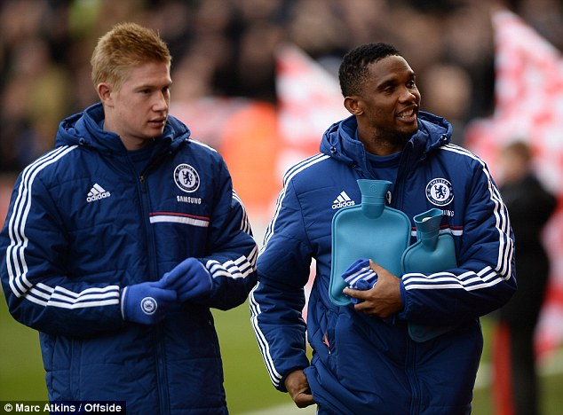 Piping hot: Samuel Eto'o holding hot water bottles while waiting to come on for Chelsea