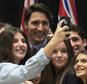 Canadian Prime Minister Justin Trudeau has his photo taken with students from a local school following an information session on climate change during a First Ministers meeting at the Museum of Nature on Monday, Nov. 23, 2015 in Ottawa. (Adrian Wyld/The Canadian Press via AP) MANDATORY CREDIT