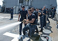 US Navy 110726-N-GZ228-131 Navy ROTC Midshipman Alex Egber is the nozzleman for his team during a damage control tug of war training exercise aboar.jpg