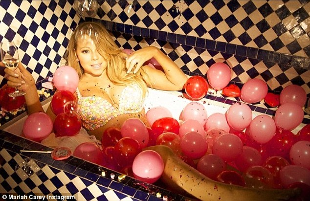 Champagne, bubbles but no Valentine: Mariah posted another sultry snap before husband Nick made it back