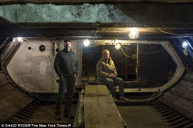 Chris Chase, left, and John Gregg in the hold of the Western Flyer, the fishing boat. Gregg and his brother are spending $2million to repair the boat, in the hopes of repurposing it as a science and education vessel